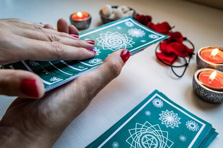 fortune teller with green tarot cards on a white wooden table background. Concept of divination