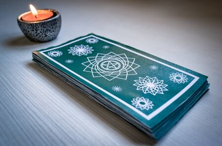 Green tarot cards with red candles on a white wooden table background. Concept of divination