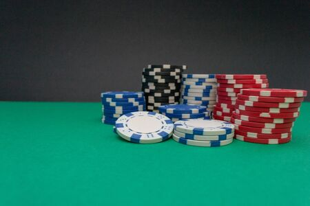 white, black, blue and red casino chips, stacked on a green background. with copy space Reklamní fotografie