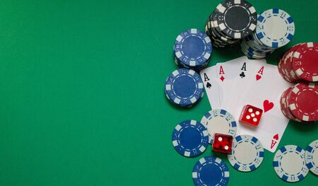 Cards, dice and poker chips on a green table, with copy space. Casino concept
