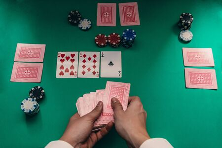 top view of poker game, with chips and cards, croupier dealing. texas holdem