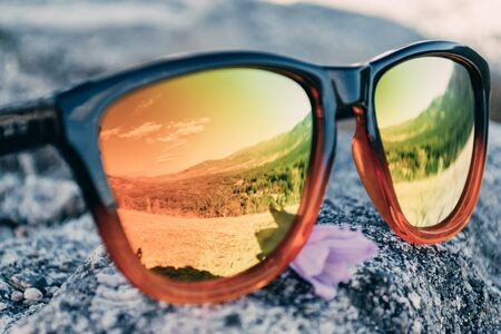 Sunglasses on a rock reflecting the mountain landscape. Concept of rural tourism