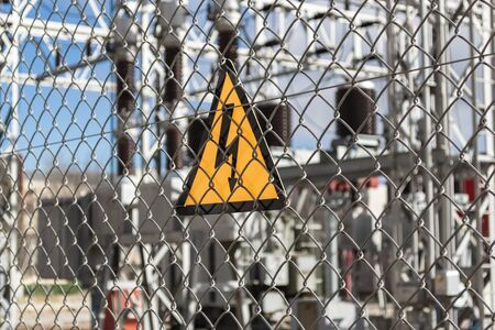 Yellow danger sign on fence surrounding power plant. ecological concept