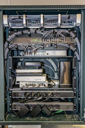 Network server rack with colored cables and internet switches in the data center. Technology concept