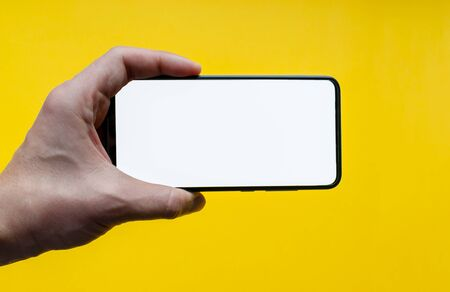 The man's hand shows a smartphone with a white screen in the horizontal position. Isolated on a yellow background