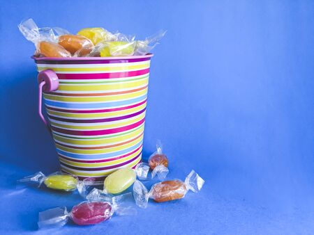 Colored bucket full of candy on a blue background. Birthday party concept Banque d'images
