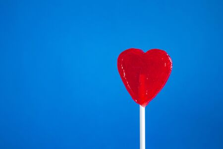 Red heart lollipop on a blue background, tasty sweets, lovers, a gift for children. Valentine's Day
