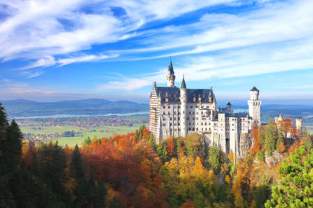 castle: Beautiful view of the Neuschwanstein castle in autumn.  Neuschwanstein Castle is a nineteenth-century palace on a rugged hill above the village near Fussen in southwest Bavaria, Germany. Today Neuschwanstein is one of the most popular of all the palaces a