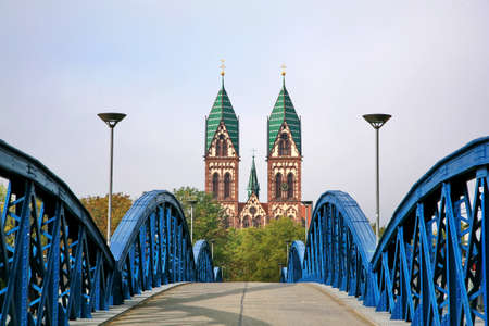 freiburg: Herz-Jesu Cathedral in Freiburg, Germany.  The Stuhlinger bridge leading to Herz-Jesu Cathedral, the gothic cathedral with a high tower in Freiburg, located in southern part of Black Forest of Germany.