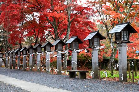 Japanese stone lanterns with beautiful maple(momiji) leaves at Nanko Park  in Fukushima prefecture, Japan