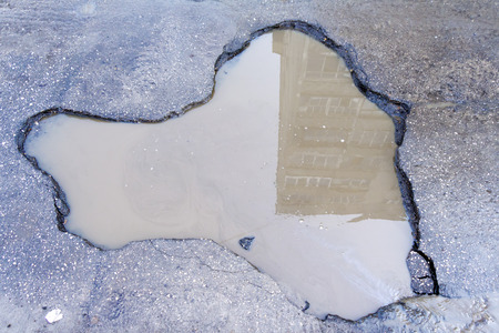 pot hole: Pit on the asphalt road filled with dirty water in which the house is reflected