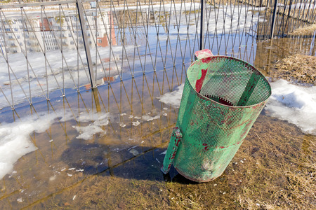 thawing: Refuse bin of red-green color in the park flooded with water from the thawing  snow