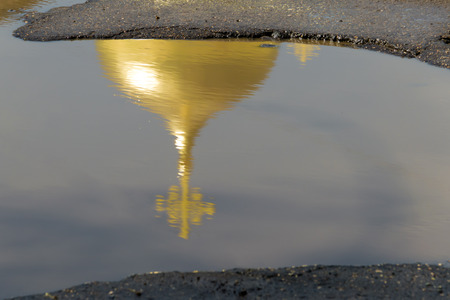 reflectivity: The yellow (gold) dome of the Church with the cross is reflected in a puddles of bad roads