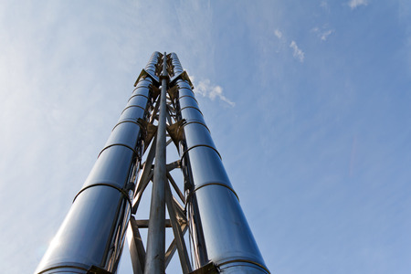 stovepipe: Two (2) new shiny smokestacks rise up into the blue sky. Of metal pipe (steel). Stock Photo