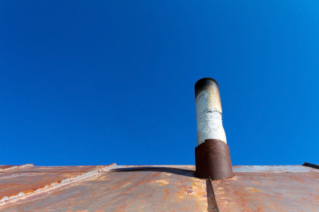 outworn: Old smoke pipe out of the rusty iron roof. In the background a clear blue sky.