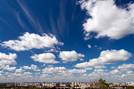 distinct: Clouds Cumulus white high in the blue sky. At the bottom a narrow strip of the city. Clouds seen to the horizon.