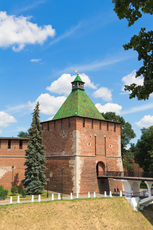 gully: Nikolskaya tower (Nicholas), the Kremlin, Nizhegorodskiy district, Nizhny Novgorod,  Russia. Tower and wall of red brick. A tourist attraction. The building is old and  vintage. Standing on the hill. Pedestrian bridge (white) to the other side of the rav