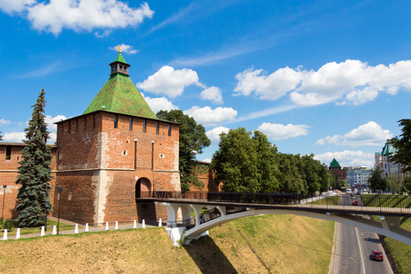 other side of: Nikolskaya tower (Nicholas), the Kremlin, Nizhegorodskiy district, Nizhny Novgorod,  Russia. Tower and wall of red brick. A tourist attraction. The building is old and  vintage. Standing on the hill. Pedestrian bridge (white) to the other side of the rav
