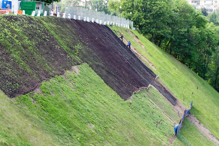 Works to strengthen the slope. The installation of the grid. Using this material can  grow grass. A struggle with the landslide. Stock Photo