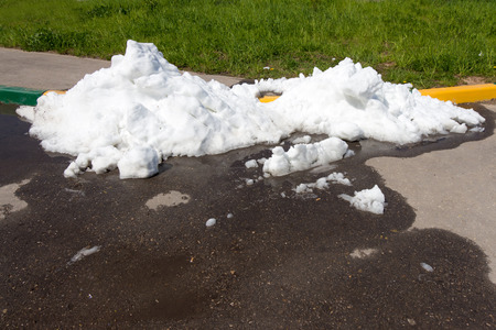 impure: A large pile of dirty snow (ice) lies in the summer on the road and melts Stock Photo