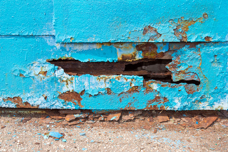 A hole in metal (steel) sheet iron blue. The edge of the hole spoiled by rust. Iron is very old.
