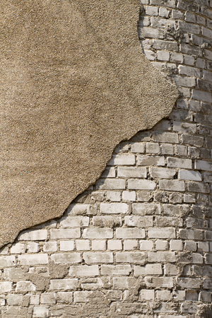The bricks white and a piece of crumbling plaster. Exterior wall coating. Stock Photo