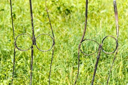 obsolescence: A fence made of rusty metal rods. Very old and rusty. A long time outdoors. The background is blurred (green grass).