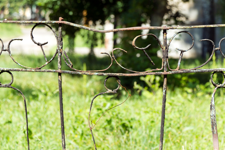 A fence made of rusty metal rods. Very old and rusty. A long time outdoors. The background is blurred (green grass).
