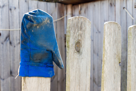 obsolescence: Blue mitten worn on the fence (wood). Gauntlet after work and dirty.
