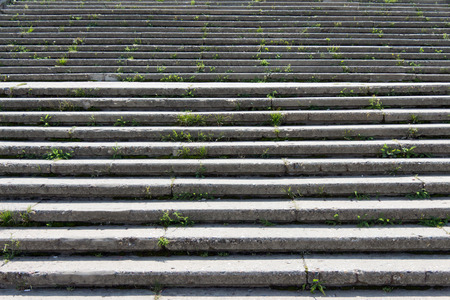 flaw: Stone (concrete) stairs with lots of steps. The light falls at an angle and creates a shadow. In the crevices the grass grow. The background is blurred.