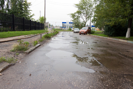 The pits on a bad road filled with rain water. On the side there are two (2) of the vehicle. In the background the blue building. Stock Photo