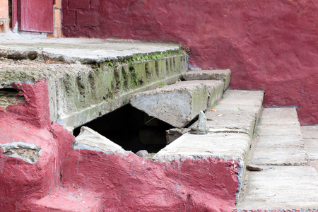 orifice: Crash of stone steps. The stairs are old and crumbling. The walls are red. The background is blurred.