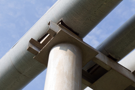 greyish: The old pipe (with stainless steel) on a background of blue sky with white clouds Stock Photo