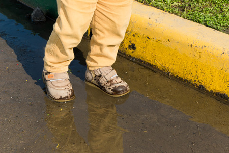 reflectivity: A small child standing in a puddle of water. His shoes wet. You only see the legs.