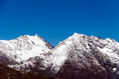 The tops of the mountains covered with snow. The fall time of the year.