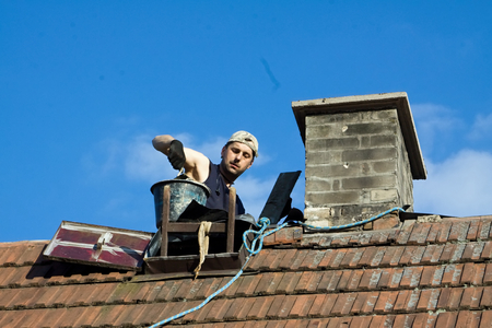 Mason worker on the roof the chimney beets