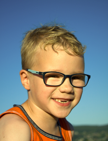sinful: blonde boy  with glasses is smiling