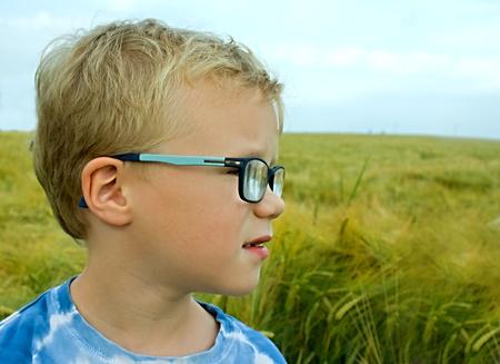 blonde boy: portrait of blonde boy with eyeglasses outdoor