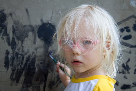 wistful: portrait of little blonde girl with brush