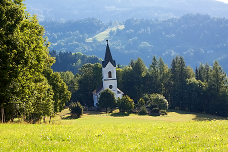 white church on the meadow and forest Stock Photo