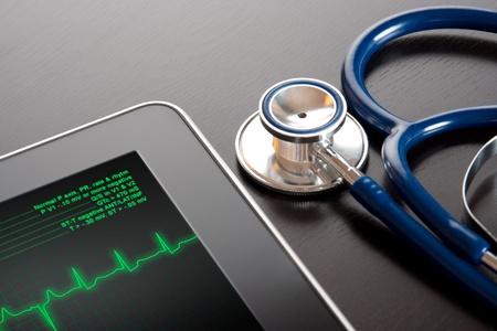 electrocardiograma: Doctor en el lugar de trabajo con el electrocardiograma pantalla tableta (ECG) y un estetoscopio Foto de archivo