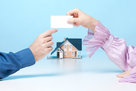 real estate agency: Real estate broker woman is giving to client her business card. Real estate agency is represented by model of house in background. Stock Photo