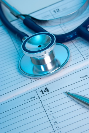 medical personal: Planning routine medical exam represented by part of stethoscope, calendar and pen. Family doctor workplace. Stock Photo