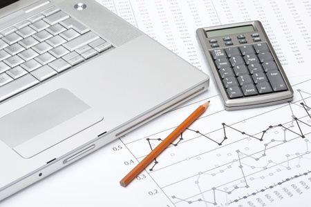 Business analyze with laptop, calculator and printed data sheet photo