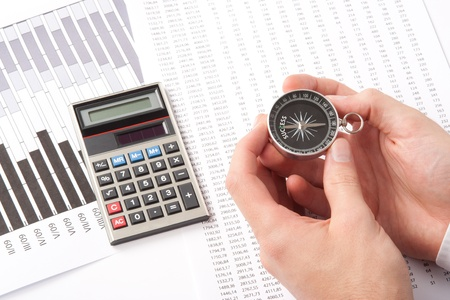 directed: Navigate to success in business and compare right direction in business concept. Man with compass directed to success word. Calculator, sheet and graph represent business. Stock Photo