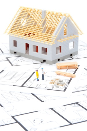 building material: Building the house concept - model of the house with building material, builder figures and blueprints Stock Photo