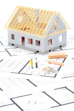 Bau des Hauses Konzept - Modell des Hauses mit Baumaterial, Baumeister Zahlen und Blaupausen