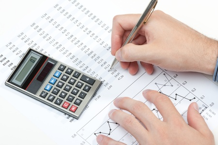 spreadsheets: Business analyst working - hand with pen, calculator, sheet and graph Stock Photo