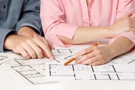 construct: Young couple planning living together in new house with interior blueprints