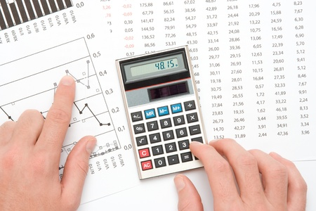 Concept of business analyst - hand with calculating on calculator, sheet and graph from top view Stock Photo - 11847070